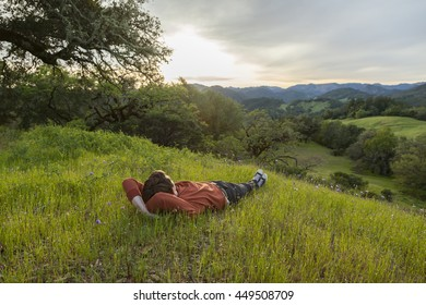 Man enjoying sunset while lying on a grassy hill in Sonoma county, California.