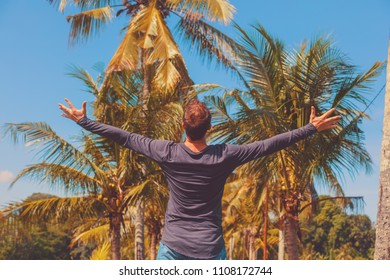 Man enjoying tropical climate with arms wide open.