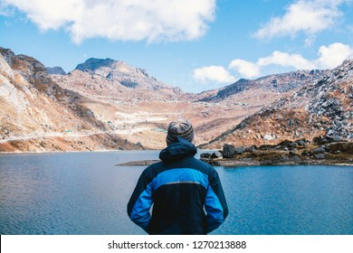 Man enjoying very much to look at blue lake with mountains background, blue sky with some clouds in day time at beginning of winter. This picture has been taken in Sikkim, India.