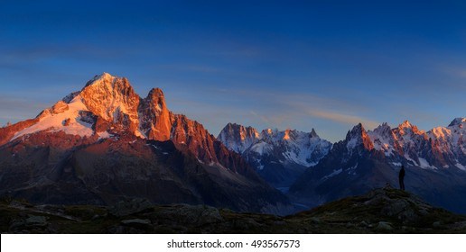 Man enjoying the view of the Alps, with Aiguille Verte and Les Drus, near Chamonix during sunset.