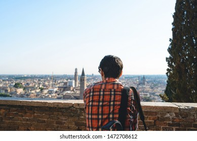 man enjoying view on city from hill