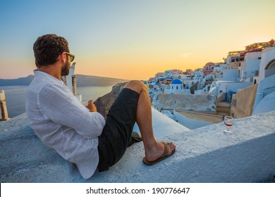 Man Enjoying Wine at Santorini Sunset