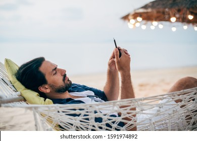 A man enjoys calm, lies in a hammock with a phone on the background of the ocean and sunset. A handsome guy looks, reads on the phone at sunset on a tropical island beach.