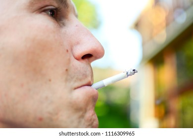 A man enjoys cigarette smoking in front of the house for smoking ban.