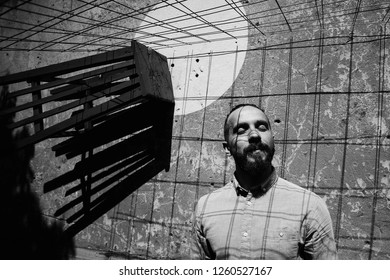 Man enjoys the hard light of the sun standing before the wall with chair on it