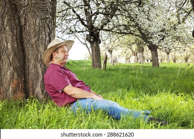 Man enjoys nature and is resting under the tree