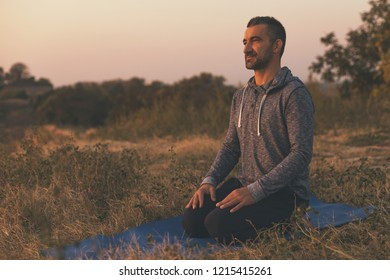 Man enjoys relaxing in the nature after exercising yoga.Image is intentionally toned.
