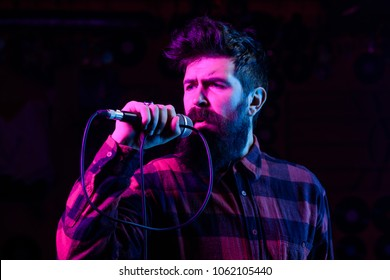 Man with enthusiastic face holds microphone, singing song, black background. Musician with beard and mustache lighted by colorful spotlight. Singer concept. Musician, singer singing in music hall.