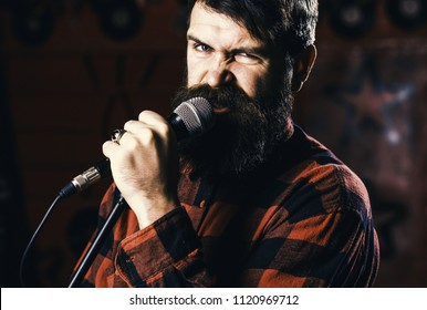 Man with enthusiastic face holds microphone, singing song, karaoke club background. Musician with beard and mustache singing song in karaoke. Rock star concept. Guy likes to sing in aggressive manner.