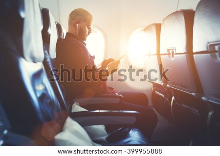 Man entrepreneur is watching video on mobile phone, while is sitting in plane near window with sun rays during his business trip. Hipster guy is listening to music in headphones via cell telephone