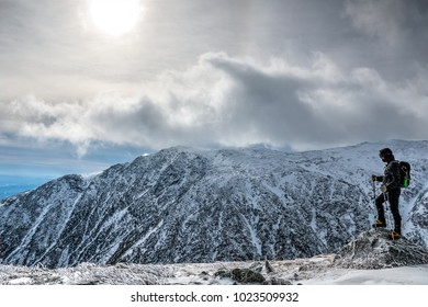 Man with equipement on the edge, hiking mount Washington in winter, looking over the ravine. New Hampshire, USA