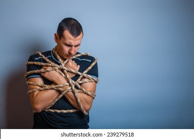 the man of European appearance brunet tied with a rope hung his head on a gray background