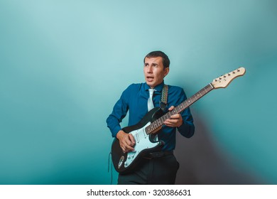 a  man of European  appearance thirty years of playing guitar on a gray background