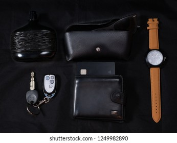 man every day carry set edc to go on dark black background - parfume, shades, glasses, wrist smart watches, car keys, wallet with credit card. low key close-up flat lay shot made from the top