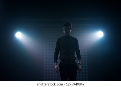 A man in everyday clothes stands on a dark stage in a dance pose. Back lighting stage light. Silhouette of a dancer.