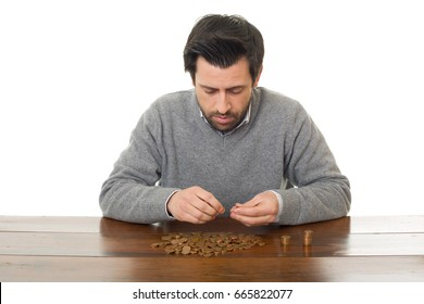 Man examines coins on a desk, isolated