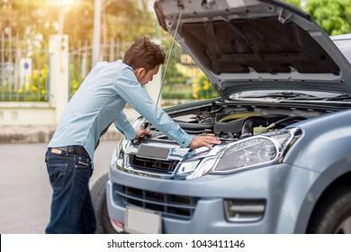 Man examining a broken car on a sunny day