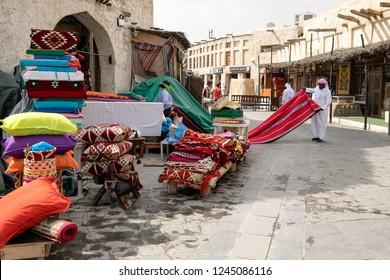 A man examining fabrics of Qatari heritage for purchase from Souq Waqif, Doha, Qatar March 2017