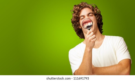 Man Examining His Teeth With Magnifier On Green Background