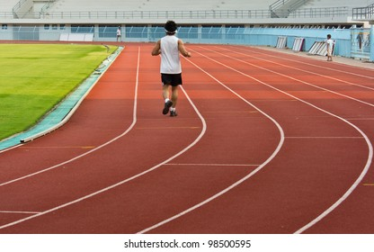 man exercise jogging and running on athletic track on stadium at sunrise