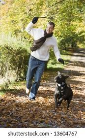 Man exercising dog in autumn woodland