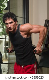 Man exercising his arm muscles on an exercise machine in a fitness center.