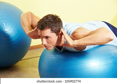 Man exercising his back on gym ball in fitness center