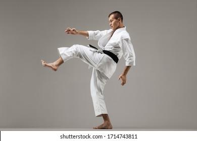 man exercising karate, against gray background