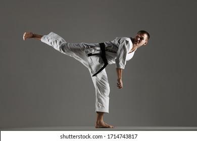 man exercising karate, against gray background, harsh side lit