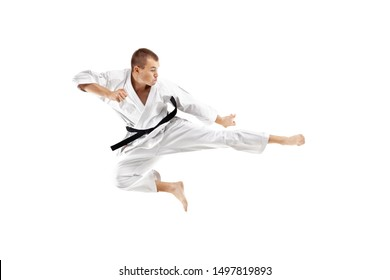 man exercising karate, kick in the air against white background