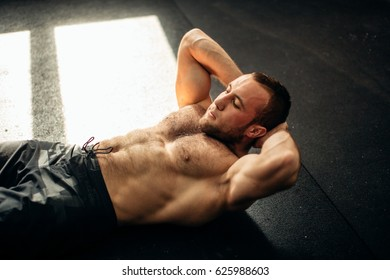 man exercising on floor. Fitness male lying on exercise with him hands behind head at gym.