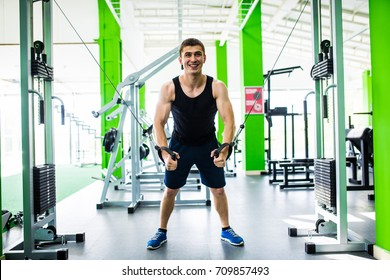 man exercising in trainer for triceps muscles in the gym