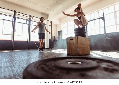 Man exercising using skipping rope and woman jumping on box in gym. Athletic couple training hard at the cross fit gym.