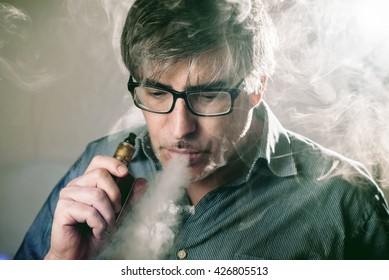 A man exhales vapor from an electronic cigarette.