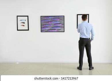Man at exhibition in modern art gallery
