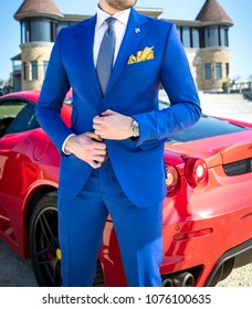Man in expensive custom tailored suit posing outdoors in front of expensive ferrari