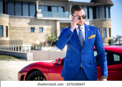 Man in expensive custom tailored suit with glasses posing outdoors in front of expensive car and house