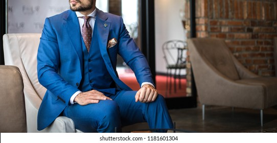 Man in expensive custom tailored suit sitting and posing indoors