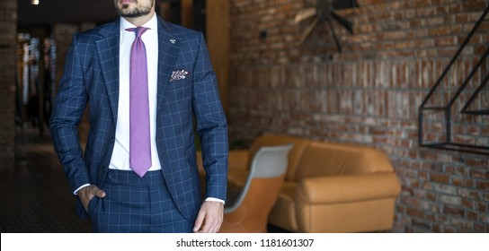 Man in expensive custom tailored suit posing indoors