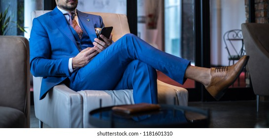 Man in expensive custom tailored suit sitting and posing indoors, and looking at his phone