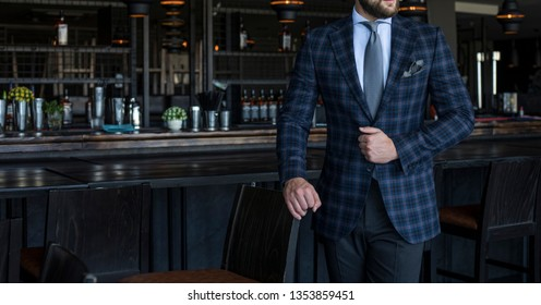 Man in expensive custom tailored suit with checked pattern standing and posing inside bar