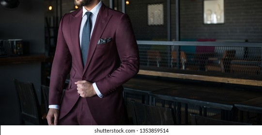 Man in expensive custom tailored suit holding his jacket and posing indoors