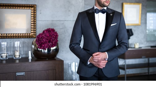 Man in expensive custom tailored tuxedo, suit posing indoors