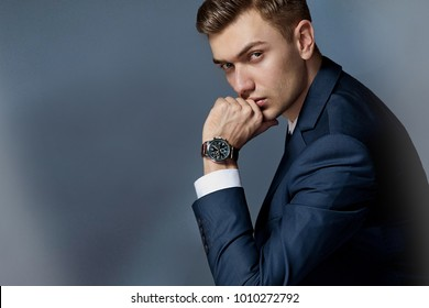 man in an expensive suit in a tie and an expensive watch posing in the studio