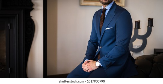 Man in expensive tailored suit sitting on couch with his hands on his legs and posing in luxury apartment