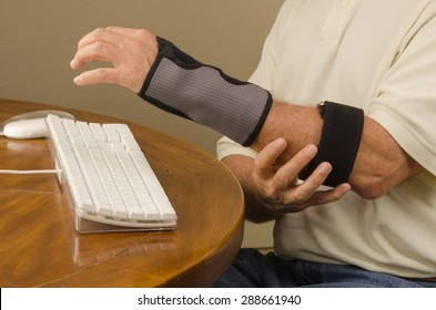 A man is experiencing computer use pain with tendinitis, carpal tunnel syndrome and repetitive stress injury very common to people who work on computers all day and jobs requiring repetitive movements