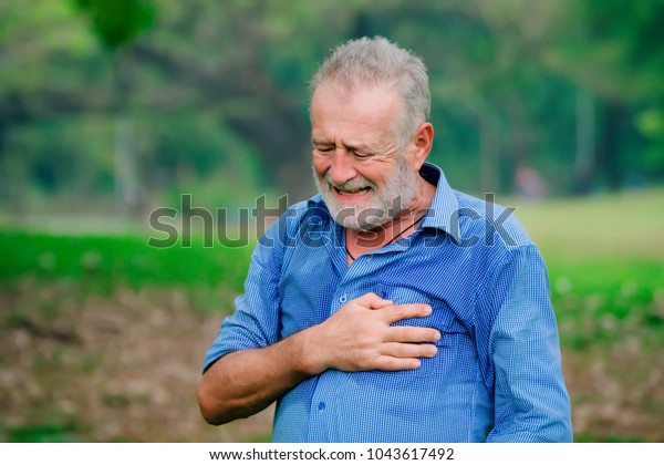 Man experiencing discomfort in his chest,Heart attack with man clutching his chest,Severe heartache,man suffering from chest pain.man with strong chest pain, horizontal