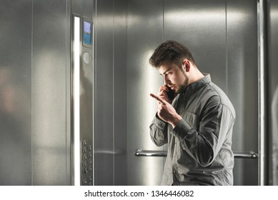 Man explaining something by the phone in the elevator wearing grey shirt. Young man employee is peacefully talking on her smartphone with her boss.