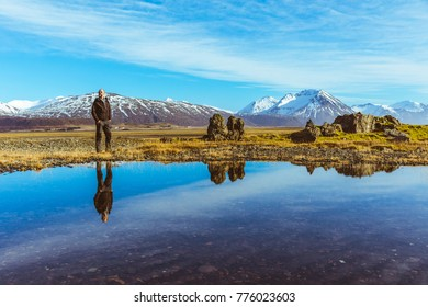 Man explorer in Iceland with his reflection on the water. Adult man walking and looking around. Majestic mountains on background, reflections on water on foreground. Travel and wanderlust concept