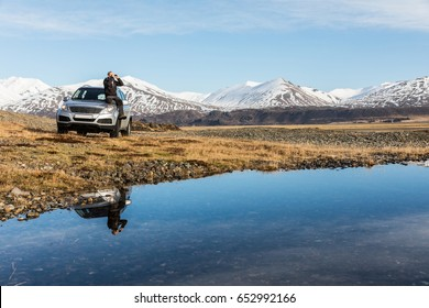 Man explorer in Iceland sitting on the car. Adult man on the bonnet looking through binoculars. Majestic mountains in background, reflections in water on foreground. Travel and wanderlust concept